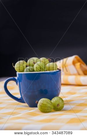 Cup With Cherry-cherry-plums. Blue Ceramic Coffeecup Overfilled With Green Cherry-cherry-plums.