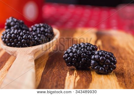 Two Focused Blackberries, Close-up. Rural Wooden Tablespoon With Berries.