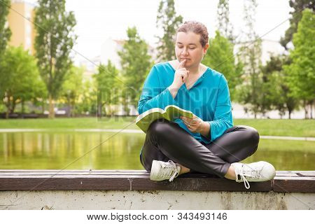 Focused Pensive Woman Enjoying Novel In Park, Sitting On Parapet Near Pond. Middle Aged Woman In Cas