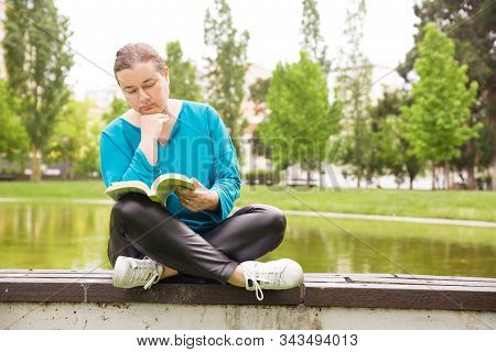 Pensive Woman Reading Book In Park, Sitting On Parapet Near Pond. Middle Aged Woman In Casual Posing
