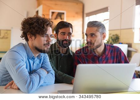 Male Coworkers Using Laptop Together, Watching Content And Talking. Business Colleagues In Casual Me