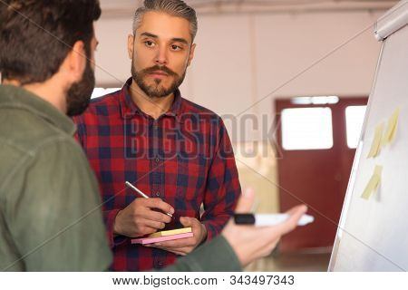 Male Coworkers Standing At Flipchart, Discussing Project. Business Colleagues In Casual Working Toge