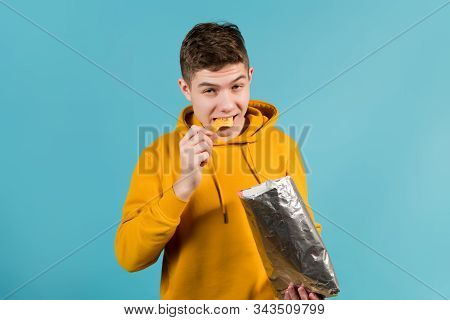 Teenager In A Yellow Sweatshirt On A Blue Background Eats Chips