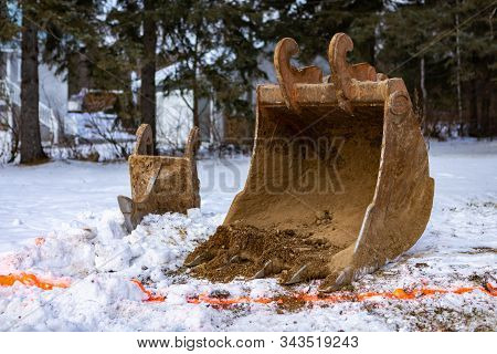 Parts Of An Excavator Are Seen On A Construction Site In Winter. A Steel Bucket With Teeth By A Pain
