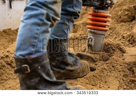 A Close Up And Selective Focus Shot On The Legs Of A Man Using A Heavy Earth Compactor On A Construc