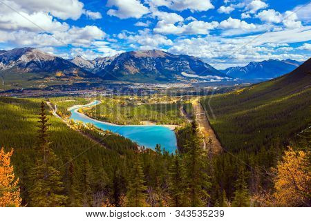 The azure icy water of the Kananaskis River in the mountain valley of Peter Lougheed Provincial Park. The autumn in the Canadian Rockies. The concept of active, ecological and photo tourism