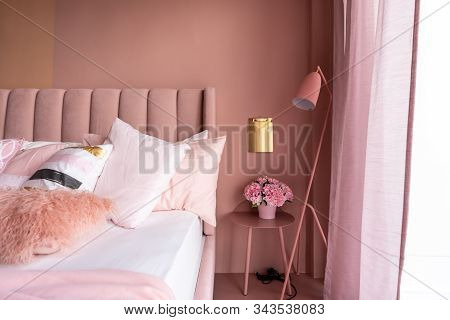 Cozy Pink Bedroom Corner With Baby Pink Velvet Fabric Bed Decorated By Blanket, Pillows And Pink Flo