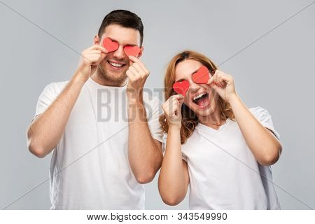 love, valentines day and relationships concept - smiling couple with red hearts instead of eyes