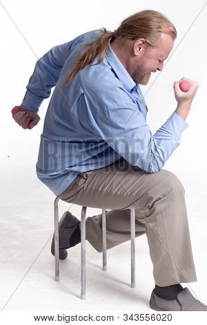 A Stout, Middle-aged, Unsportsmanlike Man In A Blue Shirt With Long Hair Sits On A Chair And Pink, L