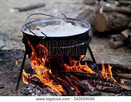 preparing food on camp - hot food boiling in the big pot over the fire