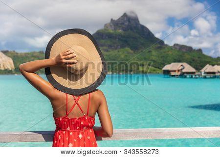 Beach vacation tourist woman looking at view of Mt Otemanu on Bora Bora luxury resort island on romantic getaway travel vacation. Tourist holding hat from behind enjoying summer holidays.