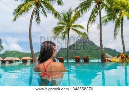 Hotel resort vacation tourist swimming in hotel pool enjoying view of famous French Polynesia honeymoon travel destination icon - Otemanu peak mount in Bora Bora island, Tahiti luxury stay getaway.
