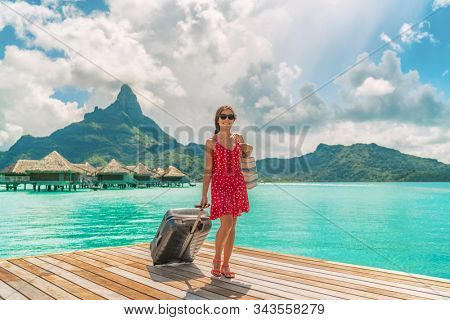Hotel luxury resort tourist woman arriving with luggage suitcase in Tahiti Bora Bora honeymoon vacation travel on arrival deck at overwater bungalows.
