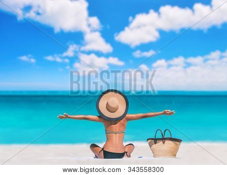 Beach woman happy carefree with open arms on Caribbean travel vacation tourist sun tanning sunbathing on towel body skincare sun exposure protection with hat enjoying summer holidays.