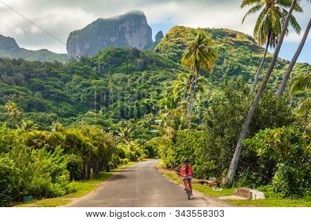 Biking tourist on summer vacation travel discovering by e-bike cycling through forest of Bora Bora island in Tahiti, French Polynesia.