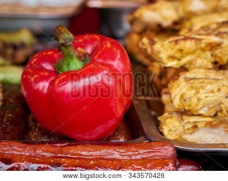 Colorful Roasted Red Pepper And Variety Of Meat Grilled Sausages Stack On Trays At Street Food Festi