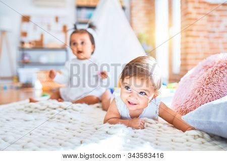 Beautiful infant happy girls playing together at home kindergarten lying on blanket