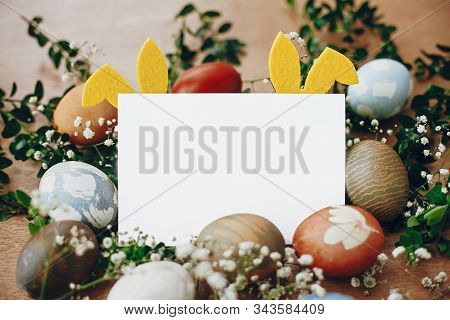 Happy Easter Card Mockup. Stylish Easter Eggs, Yellow Bunny Ears In Nest Of Spring Flowers, And Empt