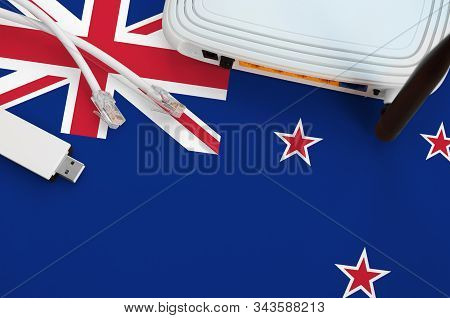 New Zealand Flag Depicted On Table With Internet Rj45 Cable, Wireless Usb Wifi Adapter And Router. I