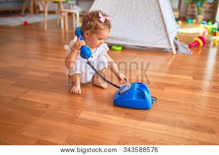 Beautiful caucasian infant playing with toys at colorful playroom. Happy and playful calling with vitange telephone at kindergarten.