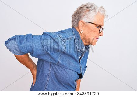 Senior grey-haired woman wearing denim shirt and glasses over isolated white background Suffering of backache, touching back with hand, muscular pain