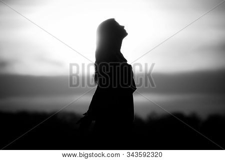 Youth Woman Soul At White Sun Meditation Awaiting Future Times. Silhouette In Front Of Sunset Or Sun