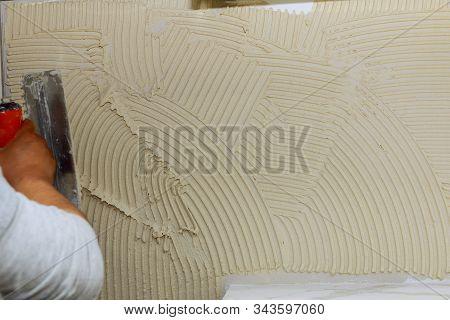 Spreading Wet Mortar Before Applying Tiles On Bathroom Floor Tile.