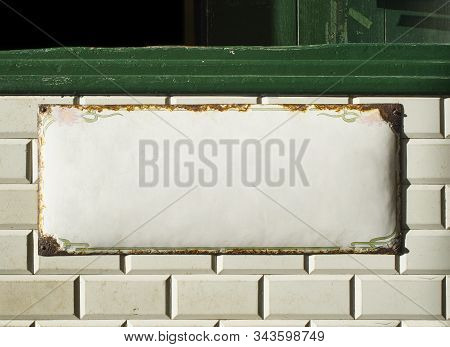 Blank Metallic Plate On An Antique Wall Tiled With Metro Tiles Background.