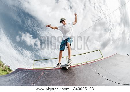 Portrait Of A Young Skateboarder Doing A Trick On His Skateboard On A Halfpipe Ramp In A Skate Park