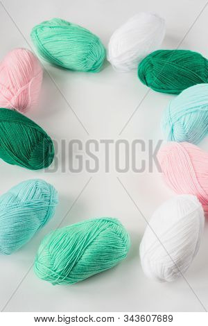 Oval Acrylic Pastel Colored Wool Yarn Thread Skeins Lying On White Background, Top-down View Flat La