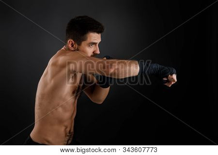 Sportsman Boxer Throwing A Fierce And Powerful Punch. Muscular Man On Black Background.