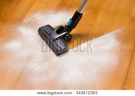 Vacuum Cleaner Brush Cleaning Flour On The Kitchen Floor
