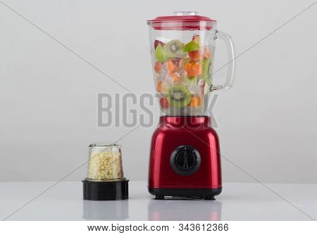 Red Blender With Fruits Inside And The Garlic Chopper Isolated On White Background