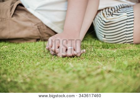 Young Couple Holding Another Hand On Dating.two Teenager On Dating Sitting On Green Grass Lawn.love
