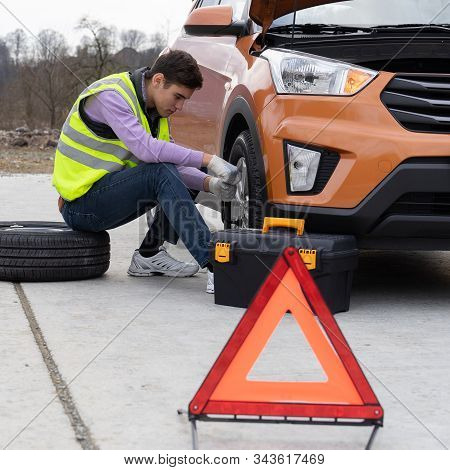 Caucasian Young Man Wearing A High-visibility Or Hi-vis Vest And Jeans Changing A Tire Sitting On St