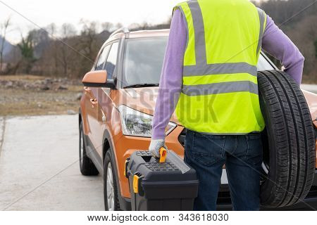 Photo Of A Mechanic Dressed In High-visibility Vest And Ready To Help, Rear View. Professional Emerg
