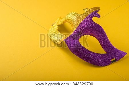 A Festive, Colorful Group Of Mardi Gras Or Carnivale Mask On A Yellow Purple Background. Venetian Ma