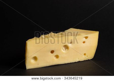 Piece Of Maasdam Cheese. Triangular Piece Of Maasdam Cheese With Large Holes On Black Background