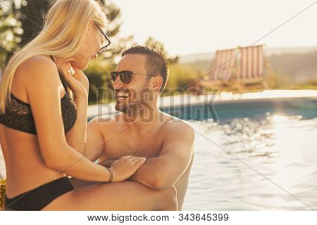 Couple In Love At A Poolside Summer Party, Sitting At The Edge Of A Swimming Pool, Sunbathing, Drink
