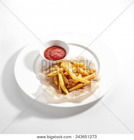 Fries or french fries on white restaurant plate with tomato sauce isolated. Sweet potato finger chips, golden french-fried potatoes or junk food snack on kraft paper closeup