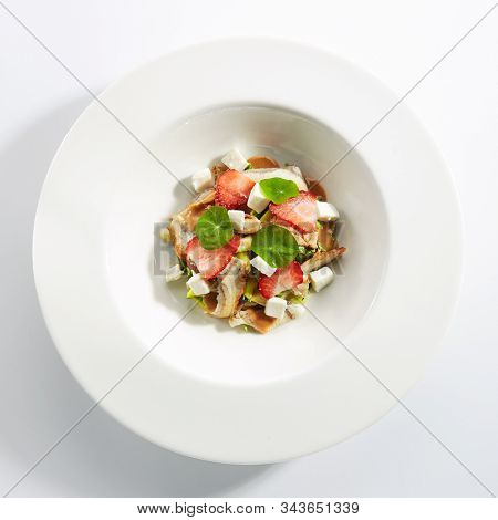Salad with smoked eel fish, avocado, feta cheese and strawberries on restaurant plate isolated. Delicious luxury seafood salat with unagi, broccoli and nasturtium leaves topview