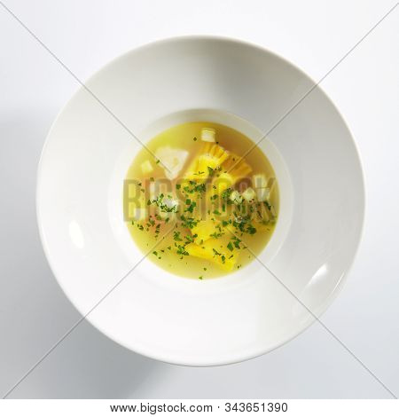 Chicken bouillon with tortellini pasta in white restaurant bowl isolated. Homemade noodle soup, clear sturdy seasoned broth with yellow egg spaghetti and greens topview