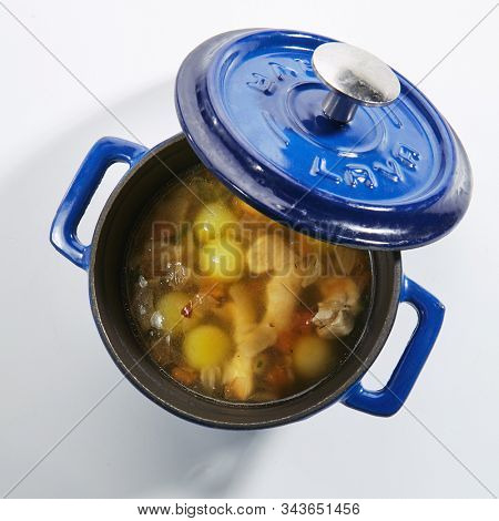 Homemade chicken soup with potatoes, carrots and onions in a blue pan isolated on white background top view. Traditional meat seasoned broth, sturdy clear bouillon in cook pot closeup