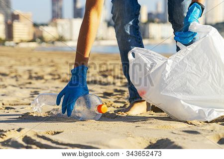 Clean Beach From Plastic. Hand Picking Up Plastic Bottle Trash From The Beach And Putting Into Plast