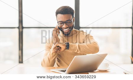 Punctuality Concept. Happy Black Man Checking Time On Wrist Watch And Talking On Mobile Phone, Empty