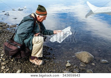 Elderly man with a camera and a photo bag examines a large piece of ice. Iceland. The lagoon Jokulsaurloun.The concept of extreme, northern and photo tourism