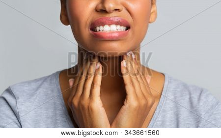 Close Up Of Afro Woman Rubbing Her Inflamed Tonsils, Tonsilitis Problem, Cropped