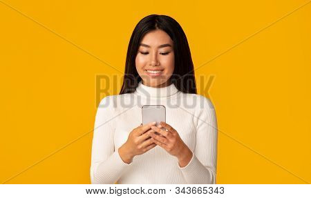 Cool Gadget. Interested Asian Girl Using Smartphone On Yellow Background