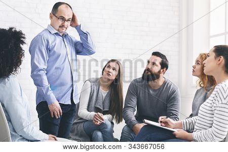 Puzzled Man Talking With Psychiatrist At Support Group Meeting, Empty Space