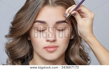 Make-up Artist Does Eyebrow Make-up To A Woman With Curly Brown Hair And Nude Make-up. Beautiful Thi
